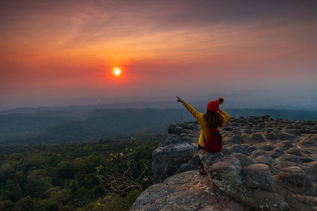 Jonge vrouw zittend op een rots in de bergen