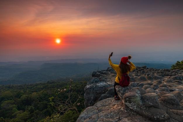 Jonge vrouw zittend op een rots in de bergen Premium Foto