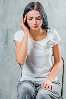 Jonge vrouw zittend op een stoel tegen een grijze achtergrond met hoofdpijn