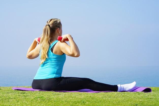 Jonge vrouw zittend op het gras met halters in handen op de achtergrond van de zee. fitness meisje doet oefeningen met gewichten op het strand onder de ochtendzon.