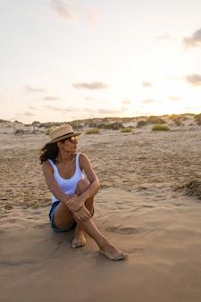 Jonge vrouw zittend op het strand