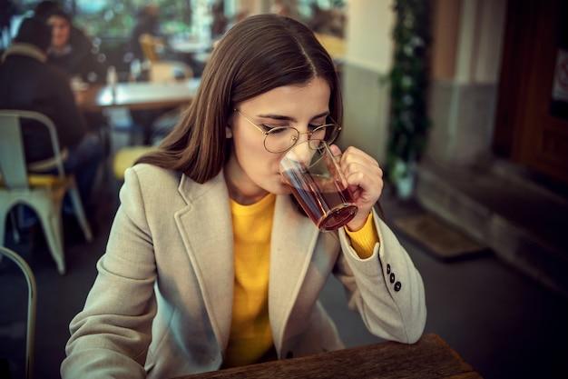 Jonge vrouw zittend op het terras van een bar en hete thee nippen.