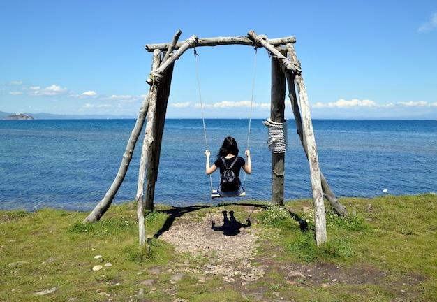 Jonge vrouw zittend op houten schommel op een achtergrond van de japanse zee