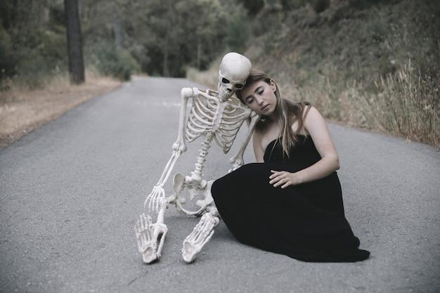 Jonge vrouw zittend op lege weg met skelet