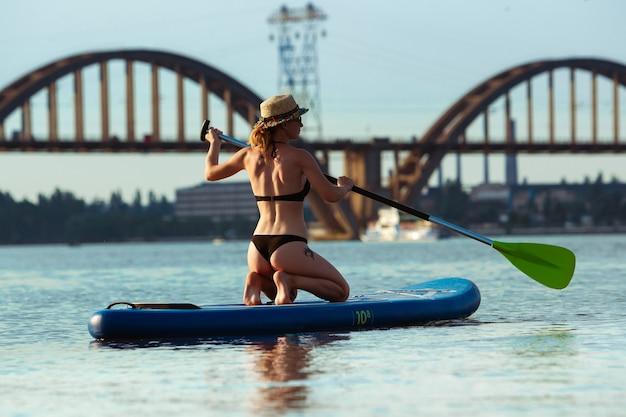 Jonge vrouw zittend op paddle board, sup. blanke vrouw op reisbord in zomeravondtijd