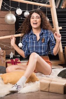 Jonge vrouw zittend op pluizig tapijt met kerstversiering