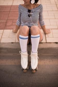 Jonge vrouw zittend op stoep met rolschaatsen