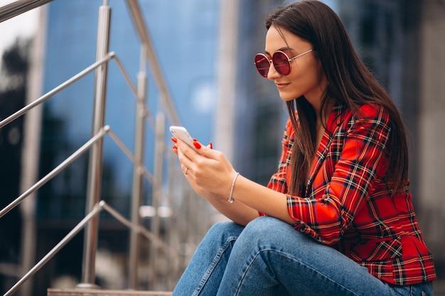 Jonge vrouw zittend op trappen en praten aan de telefoon