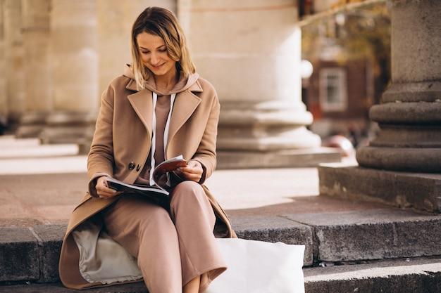 Jonge vrouw zittend op trappen in de stad en het lezen van tijdschriften