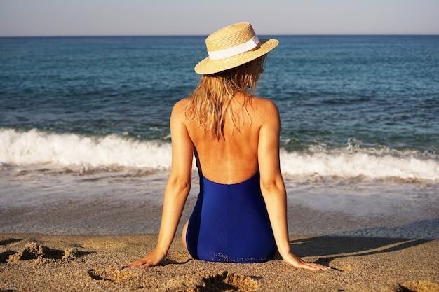 Jonge vrouw zonnebaden op tropisch strand vrouw in een blauwe zwembroek en hoed