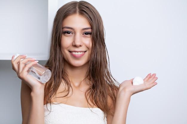 Jonge vrouw zorgt voor haar haar met behulp van natuurlijke oliën en conditioners voor haarverzorging.