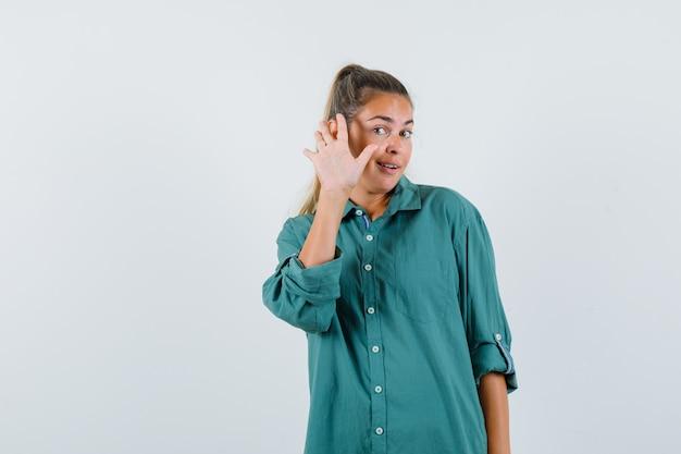 Jonge vrouw zwaaiende hand voor begroeting in blauw shirt en tevreden kijken