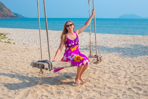 Jonge vrouw zwaait op een schommel opgehangen aan een palmboom aan de kust, reizen en toerisme naar de