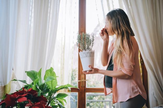 Jonge vrouw zwanger die thuis rozemarijnvaas het ruiken houdt