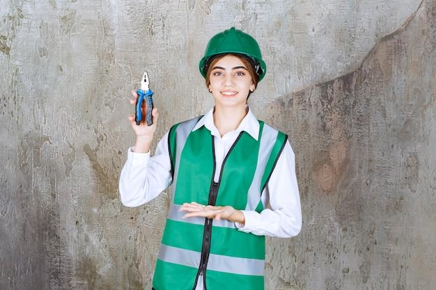 Jonge vrouwelijke aannemer in groen uniform poseren met pilaren