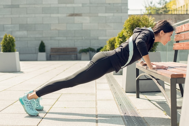 Jonge vrouwelijke actieve oefeningstraining op straat buiten push-ups