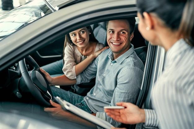 Jonge vrouwelijke adviseur en paarkopers die in nieuwe auto zitten die contract in autoshow ondertekenen. concept voor autoverhuur.
