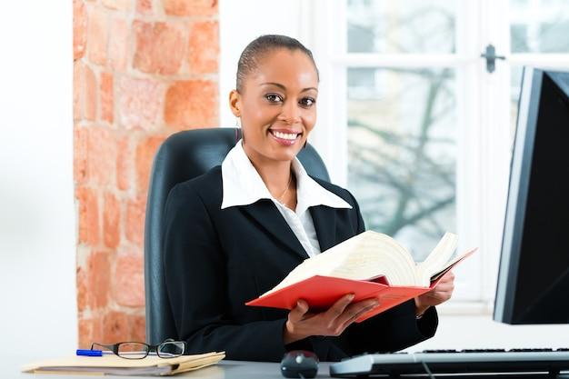 Jonge vrouwelijke advocaat die in haar kantoor met een typisch wetboek werkt en op de computer schrijft