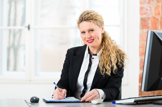 Jonge vrouwelijke advocaat of secretaresse die in haar kantoor op een computer of pc werkt
