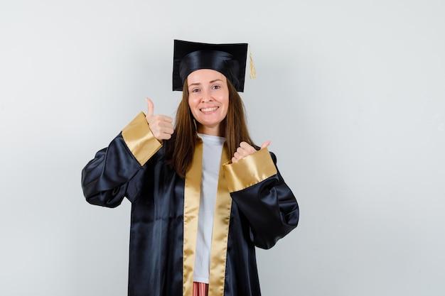 Jonge vrouwelijke afgestudeerde die dreunen in academische kleding toont en gelukkig, vooraanzicht kijkt.