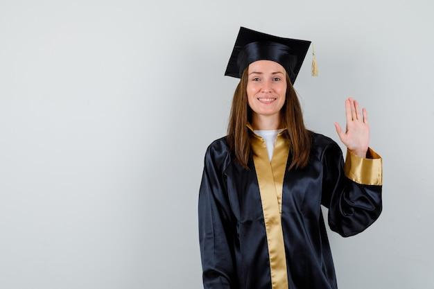 Jonge vrouwelijke afgestudeerde die palm toont voor begroeting in academische kleding en op zoek vrolijk, vooraanzicht.