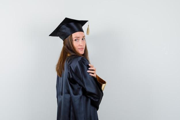 Jonge vrouwelijke afgestudeerde poseren tijdens het kijken naar camera in academische jurk en op zoek glamoureus. vooraanzicht.