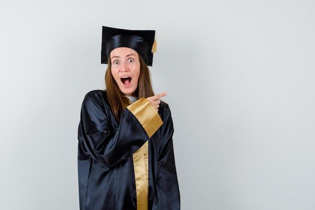 Jonge vrouwelijke afgestudeerde wijzend op de rechterbovenhoek in academische kleding en kijkt verbaasd. vooraanzicht.