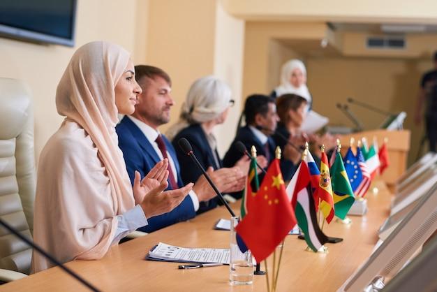 Jonge vrouwelijke afgevaardigde in hijab en haar buitenlandse collega's applaudisseren naar spreker op conferentie of forum na toespraak