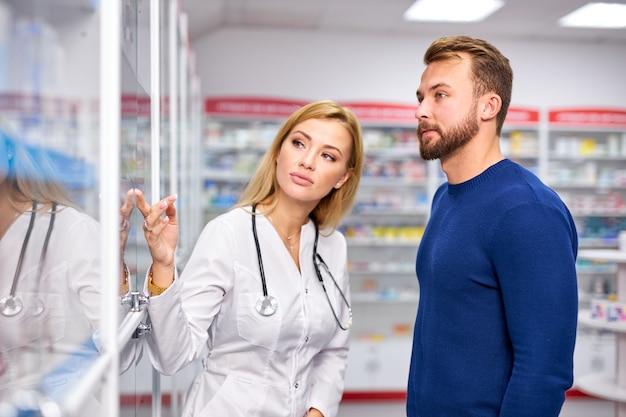 Jonge vrouwelijke apotheker die zieke mannelijke klant helpt