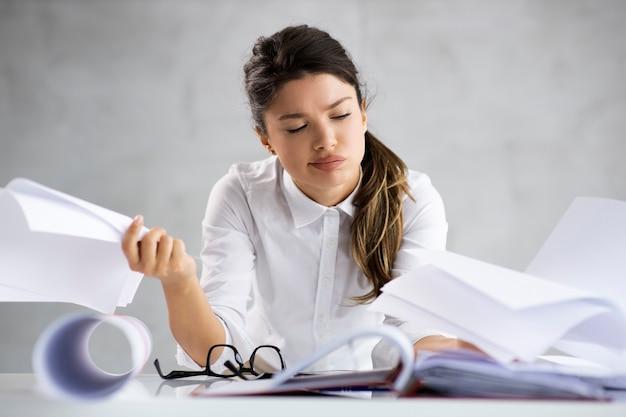 Jonge vrouwelijke architect blauwdrukken kijken en ze verveelt zich.