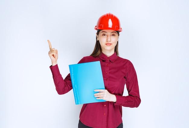 Jonge vrouwelijke architect in rode helm met documenten en wijzend op een witte achtergrond.