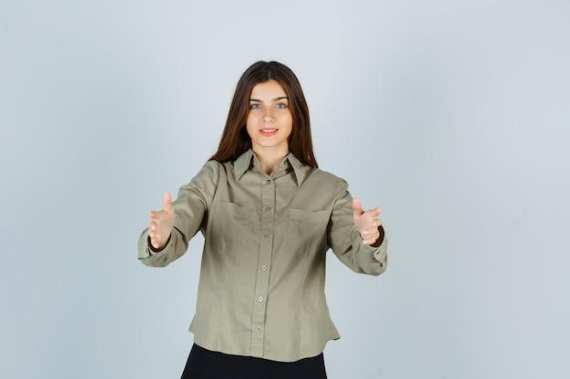 Jonge vrouwelijke armen openen voor knuffel in shirt, rok en er positief uitzien, vooraanzicht.