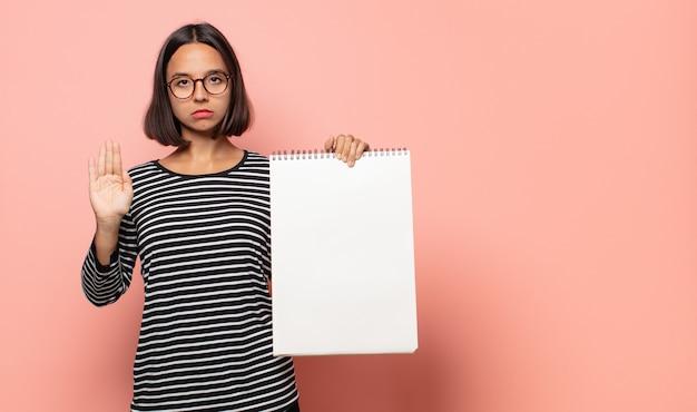 Jonge vrouwelijke artiest die er serieus, streng, ontevreden en boos uitziet en een open palm laat zien die een stopgebaar maakt