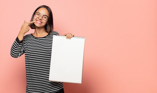 Jonge vrouwelijke artiest glimlachend vol vertrouwen wijzend naar eigen brede glimlach, positieve, ontspannen, tevreden houding