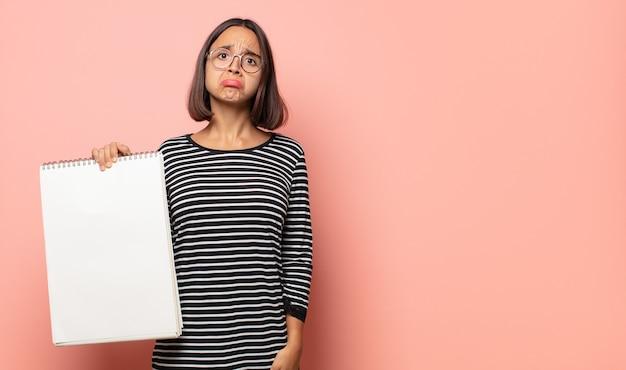 Jonge vrouwelijke artiest voelt zich verdrietig en zeurt met een ongelukkige blik, huilt met een negatieve en gefrustreerde houding