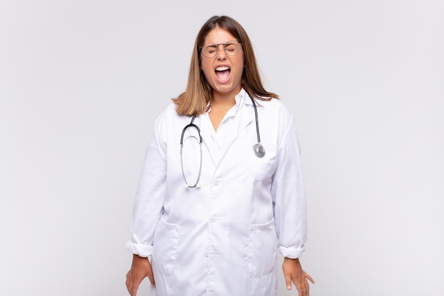 Jonge vrouwelijke arts die agressief schreeuwt, er erg boos, gefrustreerd, verontwaardigd of geïrriteerd uitziet, nee schreeuwt