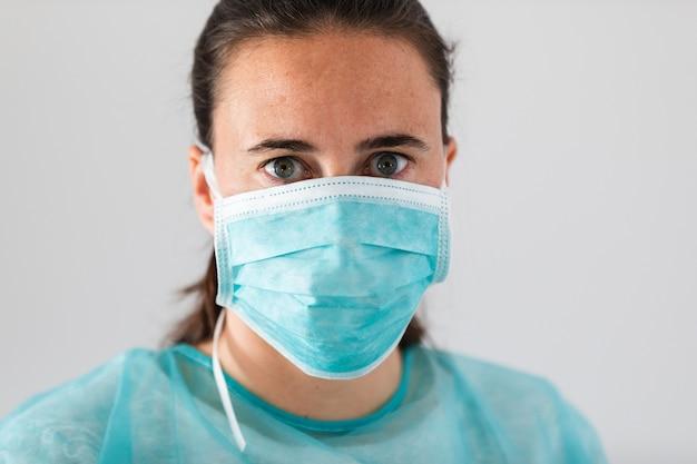 Jonge vrouwelijke arts die beschermend masker draagt tegen coronavirus. medische persoonlijke beschermingsmiddelen.