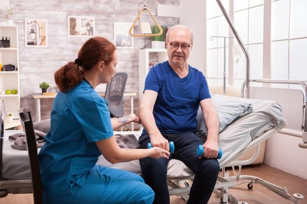 Jonge vrouwelijke arts die de oude man helpt met zijn lichamelijke behandeling.