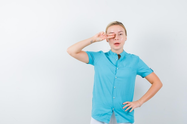 Jonge vrouwelijke arts die een pistoolgebaar op het oog laat zien terwijl ze de hand op de heup houdt