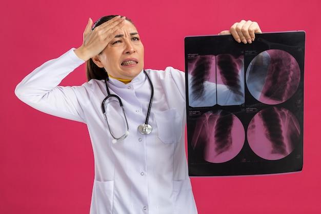 Jonge vrouwelijke arts die een röntgenfoto van de longen vasthoudt en er verward uitziet met de hand op haar hoofd