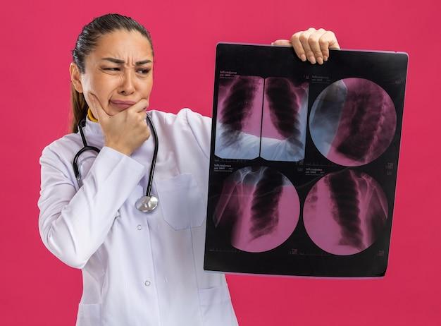 Jonge vrouwelijke arts die een röntgenfoto van de longen vasthoudt en ernaar kijkt met een verwarde uitdrukking