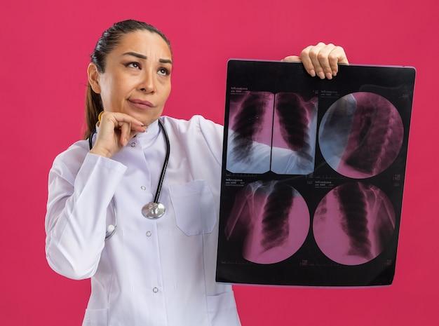 Jonge vrouwelijke arts die een röntgenfoto van de longen vasthoudt en verbaasd opkijkt