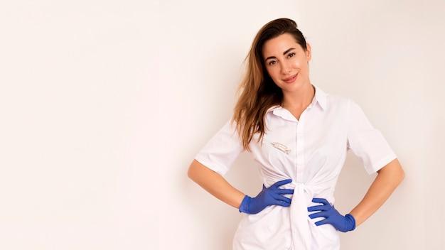 Jonge vrouwelijke arts die en over witte muur glimlacht stelt