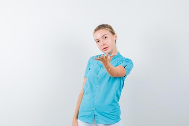 Jonge vrouwelijke arts die gebaar toont in medisch uniform, masker en er mooi uitziet