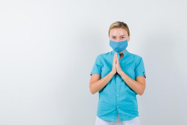 Jonge vrouwelijke arts die gevouwen handen toont in een smekend gebaar in medisch uniform
