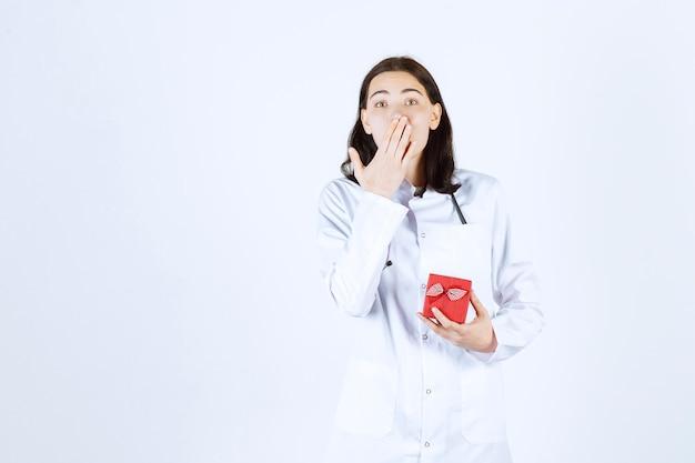 Jonge vrouwelijke arts die haar kleine giftbox houdt terwijl zij haar hand legt