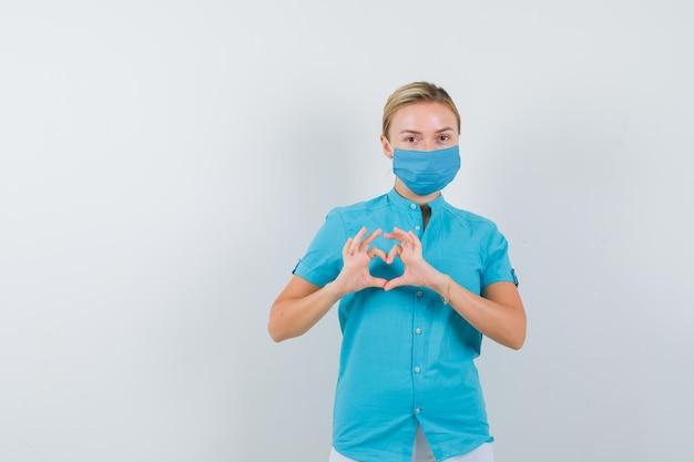 Jonge vrouwelijke arts die hartgebaar toont in medisch uniform, masker en er schattig uitziet