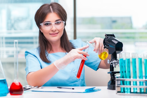 Jonge vrouwelijke arts die in het laboratorium werkt