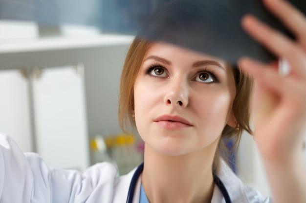 Jonge vrouwelijke arts die longenröntgenstraal bekijkt