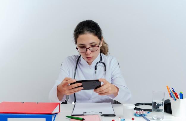 Jonge vrouwelijke arts die medische mantel en stethoscoop en bril draagt die aan bureau met medische hulpmiddelen zit die geïsoleerde mobiele telefoon met behulp van